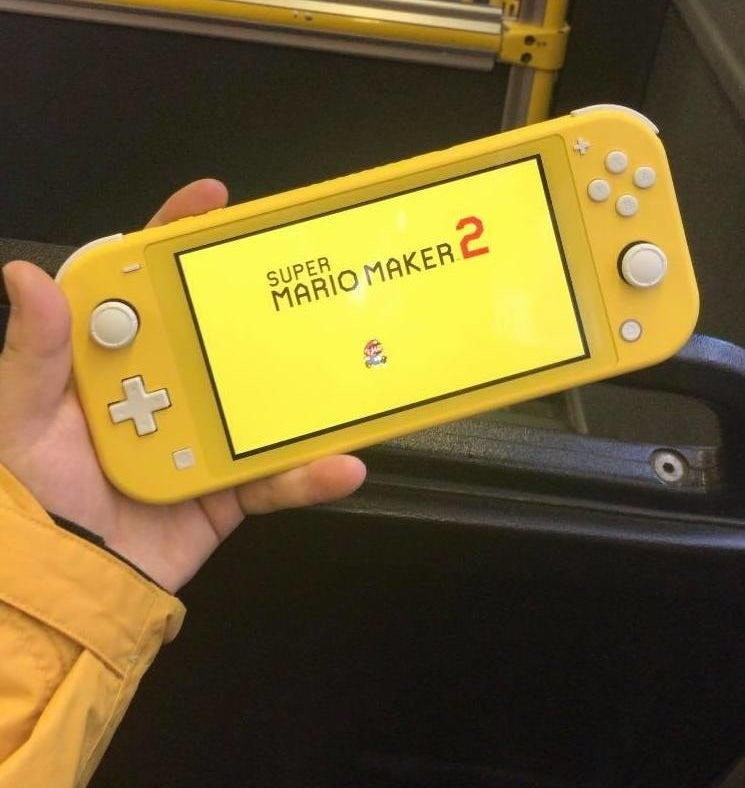 A person's hand holding a Nintendo Switch Lite console