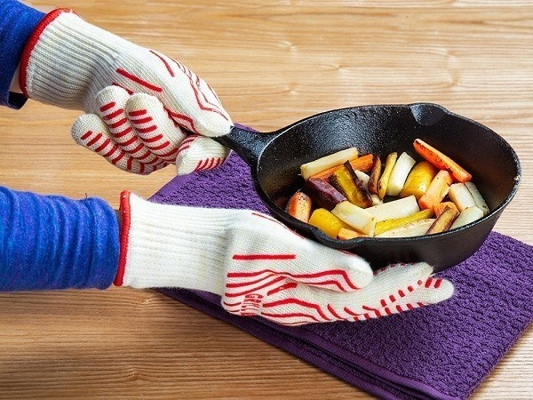 Hand wearing gloves holding a skillet of food