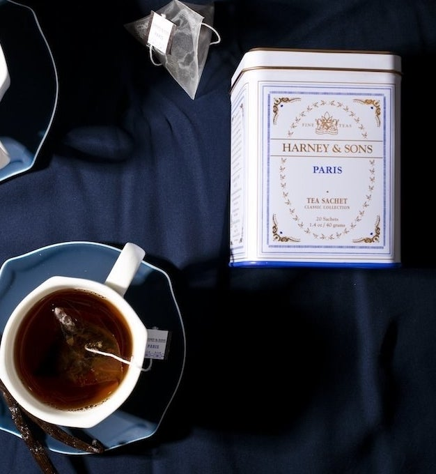 the white tin next to a cup of tea
