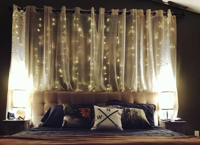 Reviewer's string lights above their quilted headboard