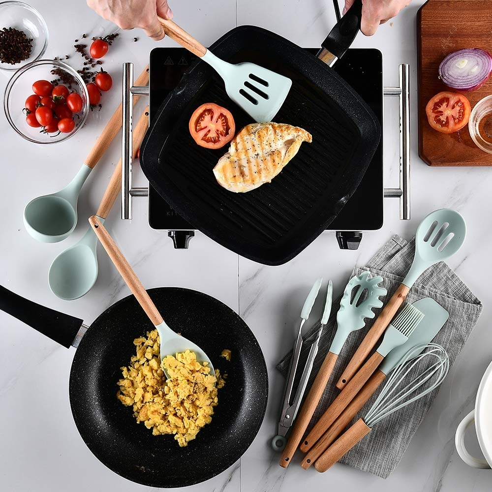 The kitchen utensils being used on a grill and in a pan