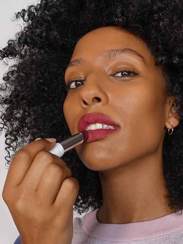 Model applying lightweight lipstick