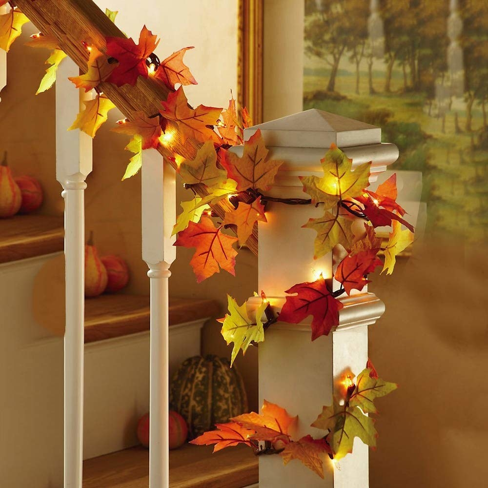 A staircase with a string of lights and coloured leaves wrapped around the handrail
