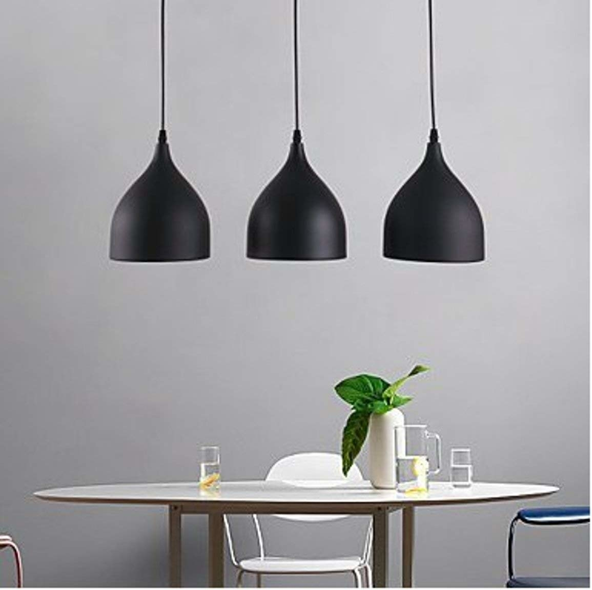 Three black pendant lights hanging above a circular dining table.