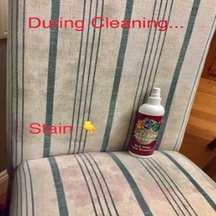 a bottle of wine stain remover next to a stained chair