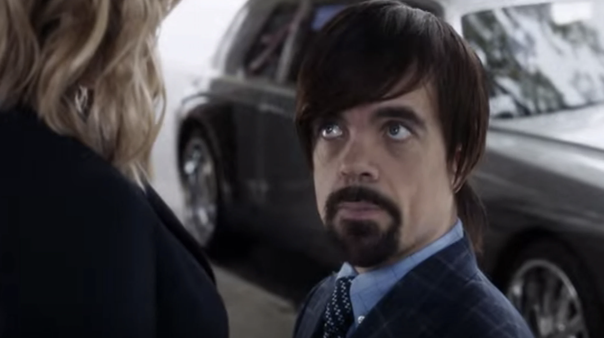 Peter Dinklage in a wig with long bangs that swoop to one side