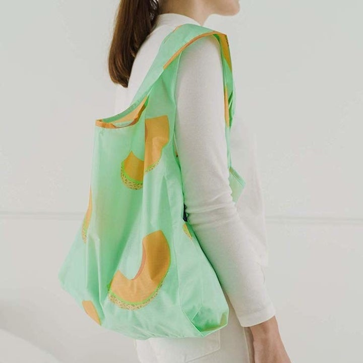 model holding a green bag with cantaloupe slices all over it
