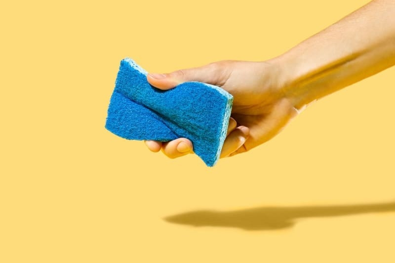 hand holding the blue sponge