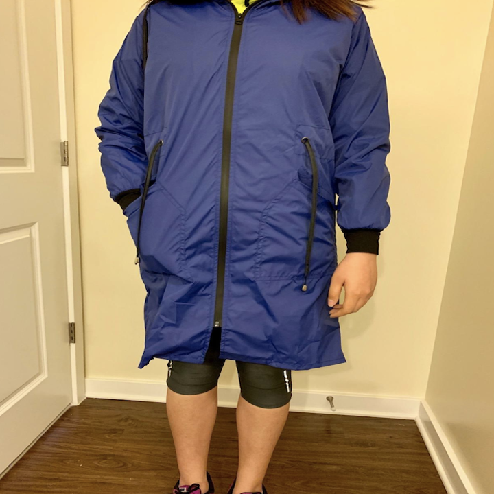 reviewer wearing the blue raincoat zipped up