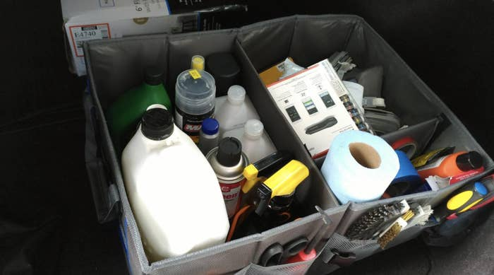 reviewer's photo of the square car trunk organizer with an open top showing different compartments filled with stuff. There are also pockets on the side.