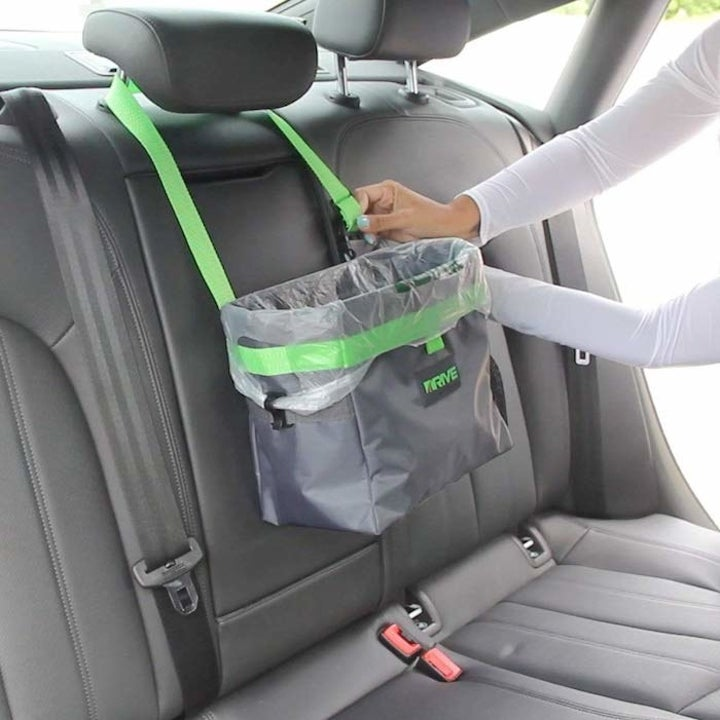 a gray and green trashcan made with a canvas-like material with a trash bag liner inside and attached by a green strap to a headrest in a car's backset