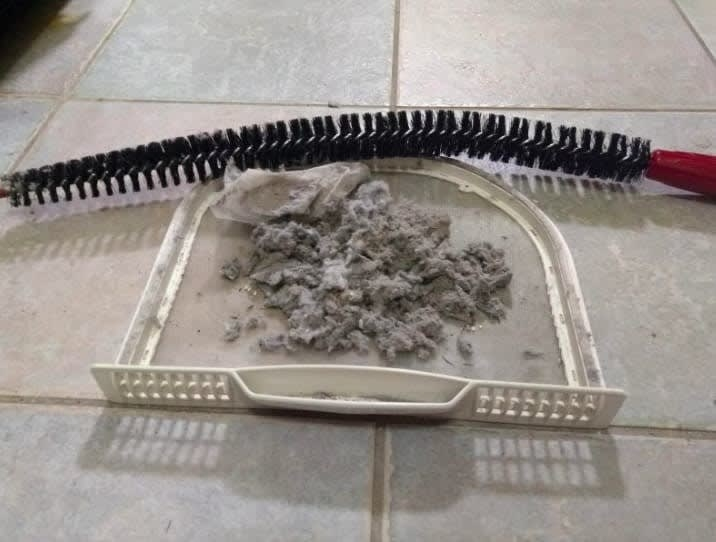 A lint trap and the lint brush with a big pile of lint