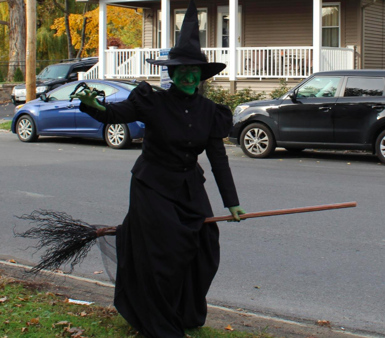 reviewer wearing long black dress with black pointy hat and broomstick