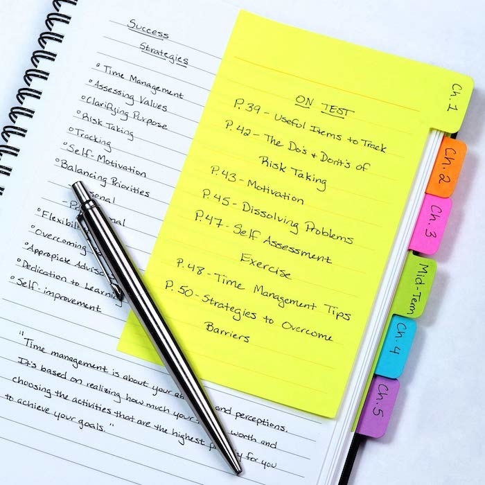 a sticky note divider on the side of a page from a note book with other sticky notes poking out from unseen pages