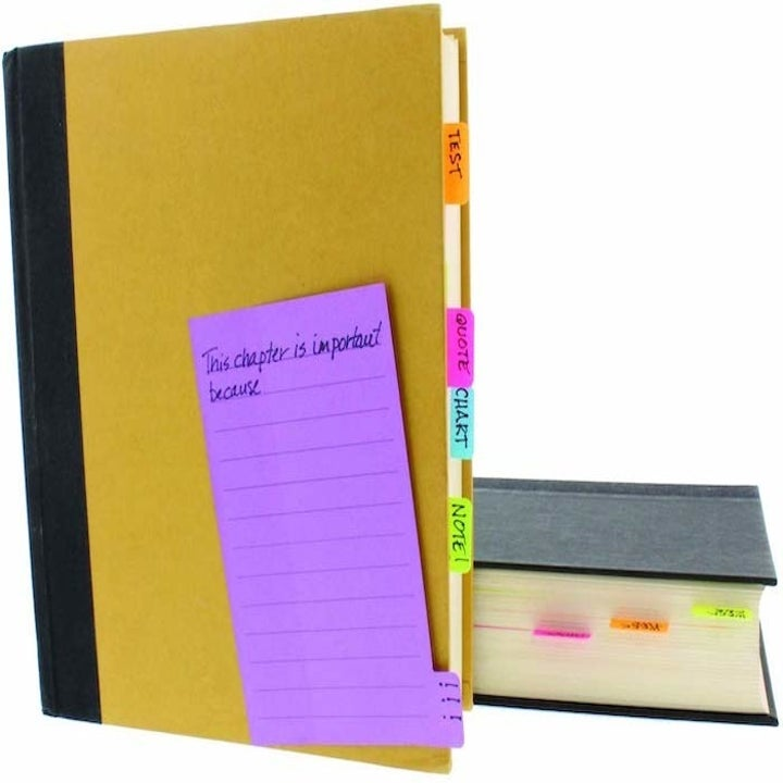 closed book with small tabs from the larger sticky notes sticking out of the pages