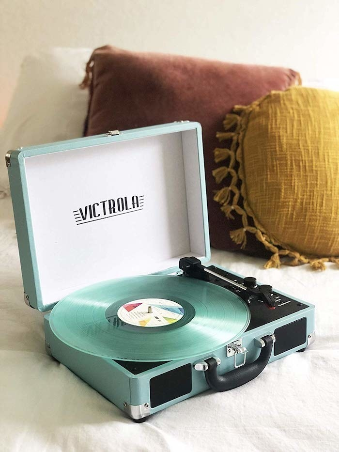a mint green record player with a matching mint green record sitting on it