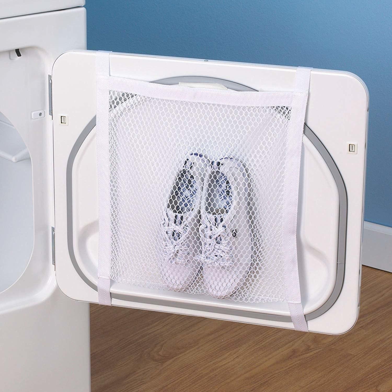 Sneakers inside mesh bag hanging from washer door