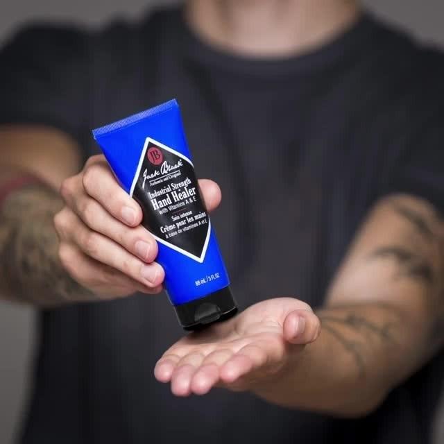 A model holding the bottle of Jack Black Hand Healer cream