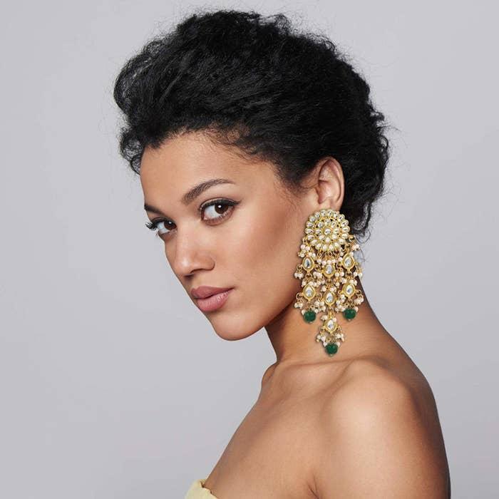 A model showcasing the white, gold, green kundan chandbalis.