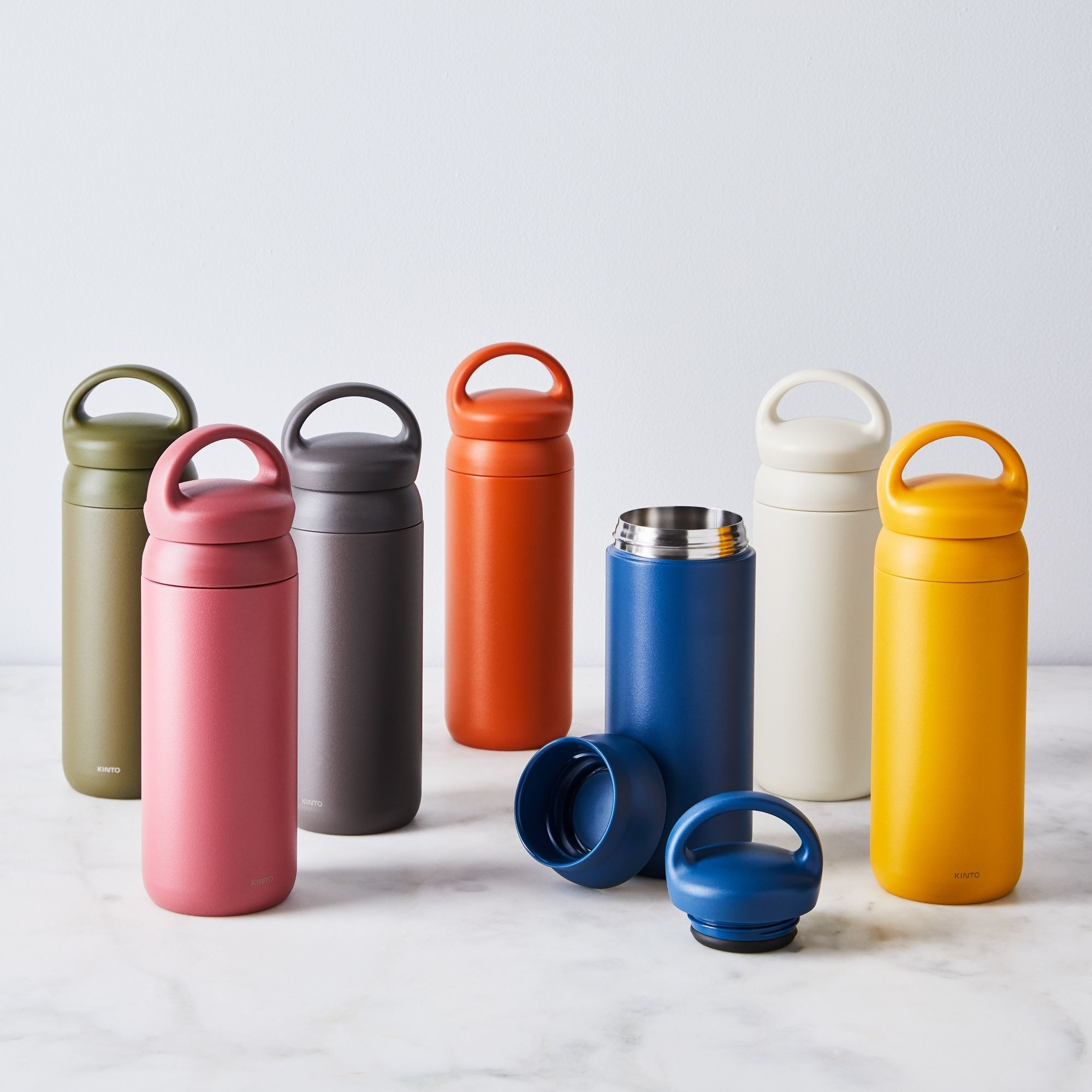 Seven travel tumblers in different colors standing upright on white marble surface