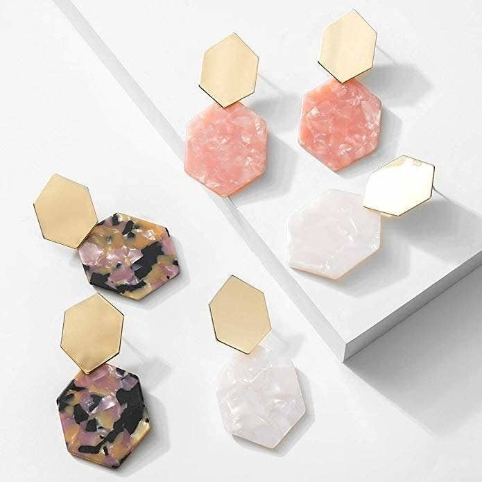 Three pairs of the earrings in a geometric design with a top gold piece and a resin bottom piece in different colors