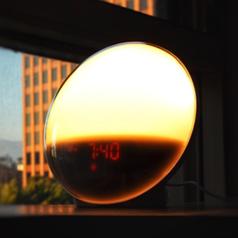 the alarm clock half-lit in a light yellow light. It says 7:40