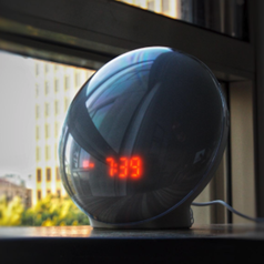 """the circular sunrise alarm clock with the time """"7:39"""" reflected"""