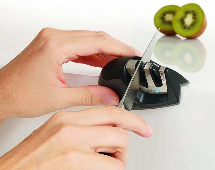 model's hand sliding a knife through the slot on the knife sharpener
