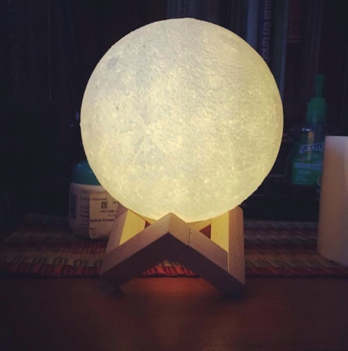 circular light glowing that looks like a mini-moon sitting on a wooden stand