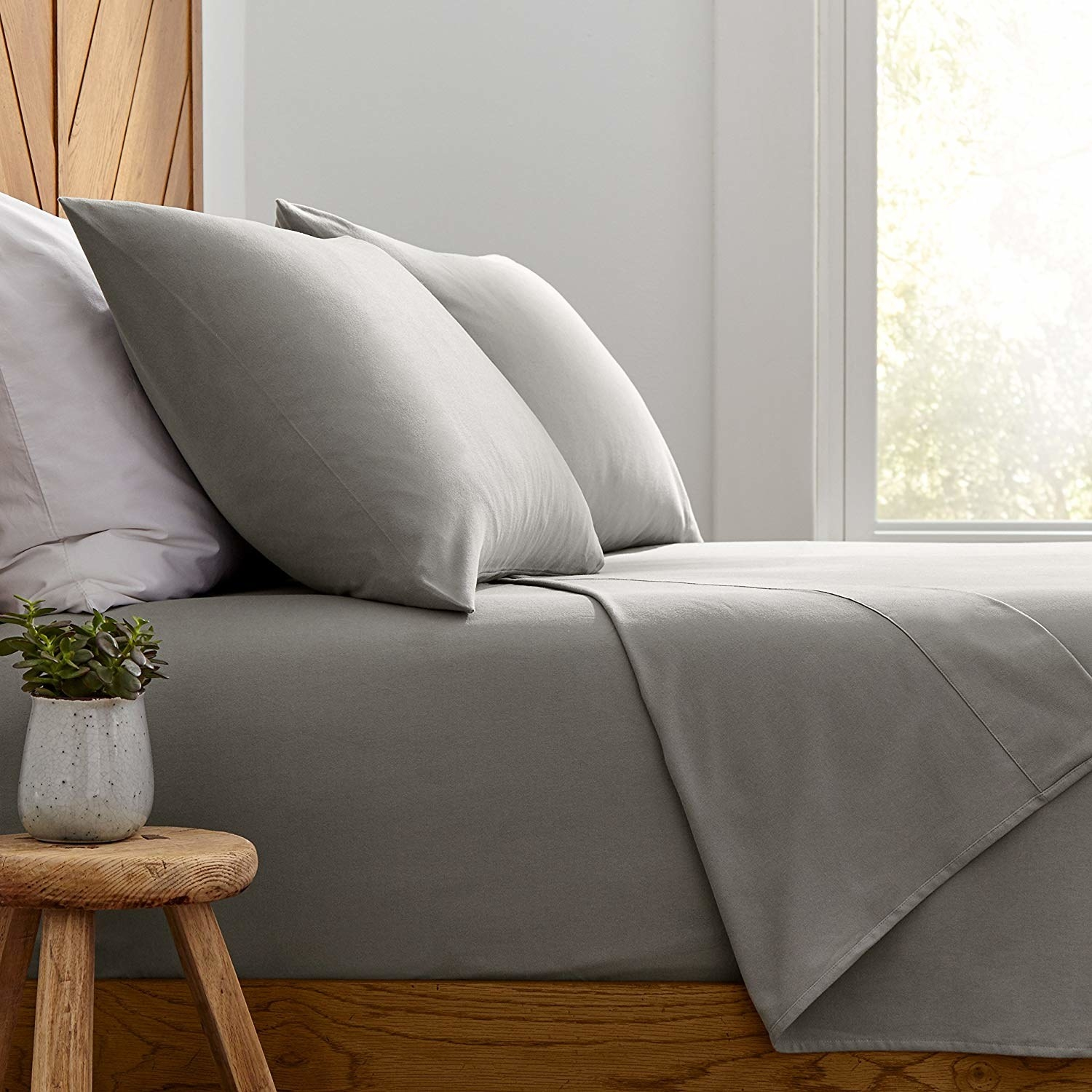 The sheets in grey on a bed