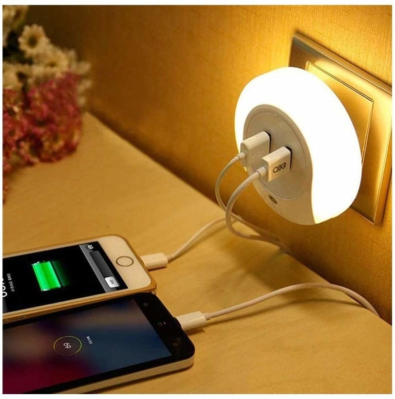 A night lamp plugged into a wall socket and two phones charging off it
