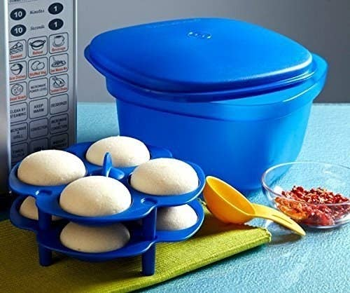 The multipurpose cooking tool pictured with a measuring spoon and cooked idlis in its idli maker.