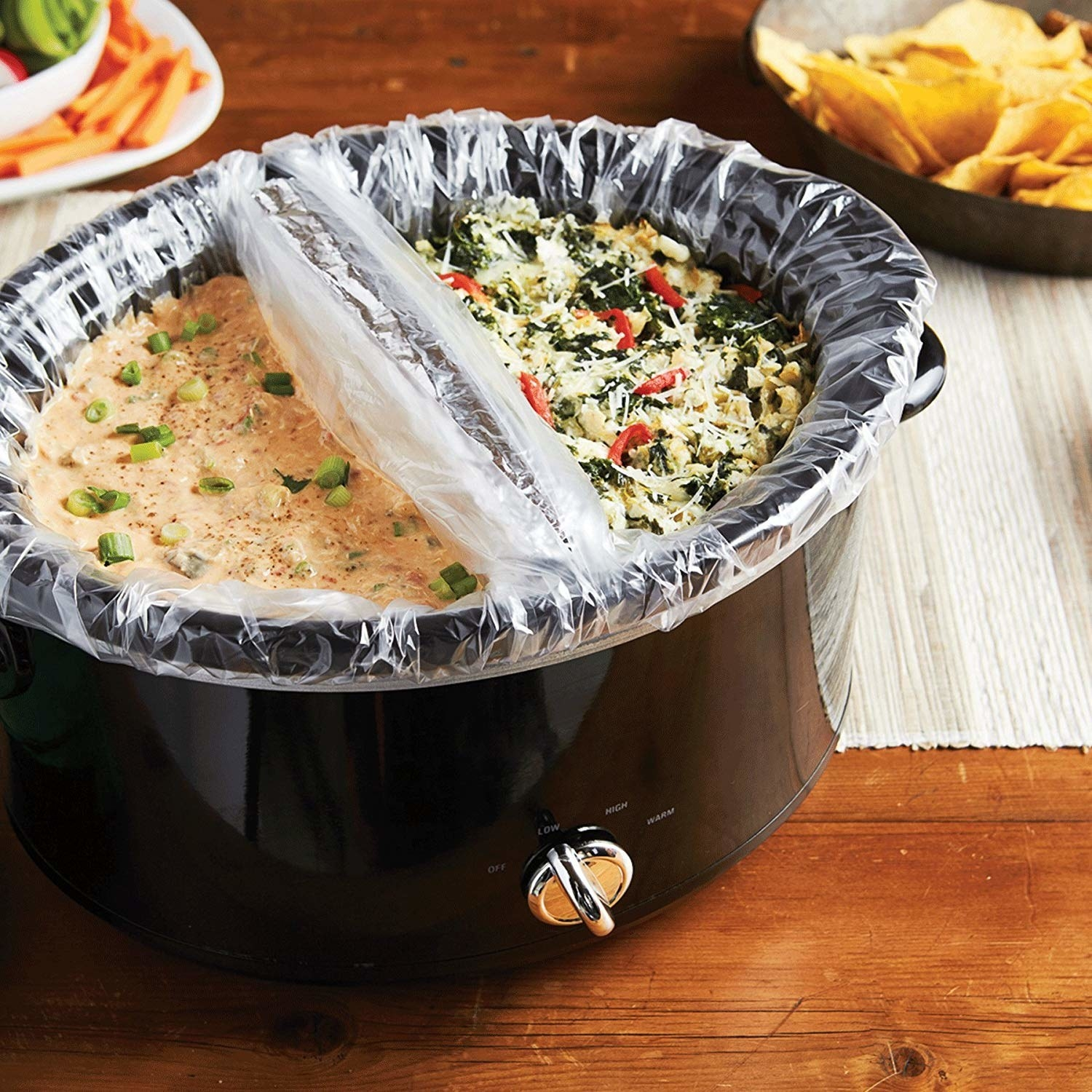 A two-compartmented slow cooker with liners on either side, filled with dips and side salads