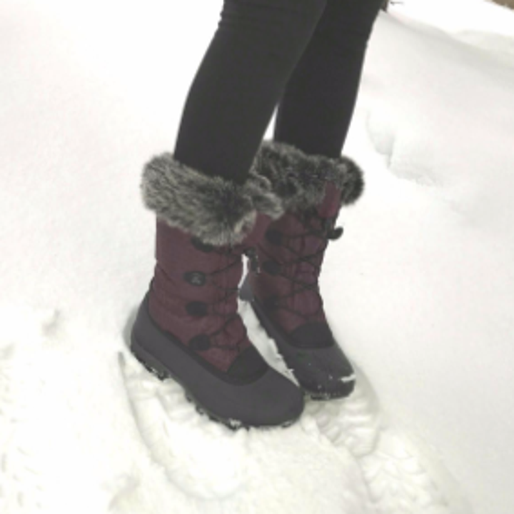 a reviewer wearing snow boots in purple with faux fur at the top
