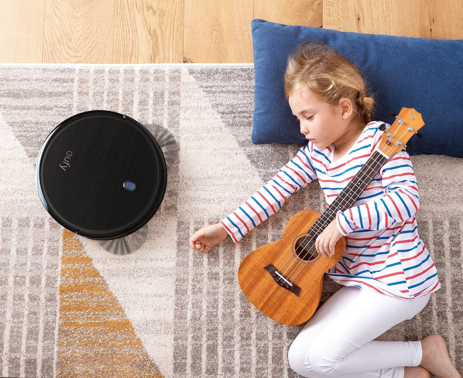 Young girl lying on ground with guitar next to robot vacuum
