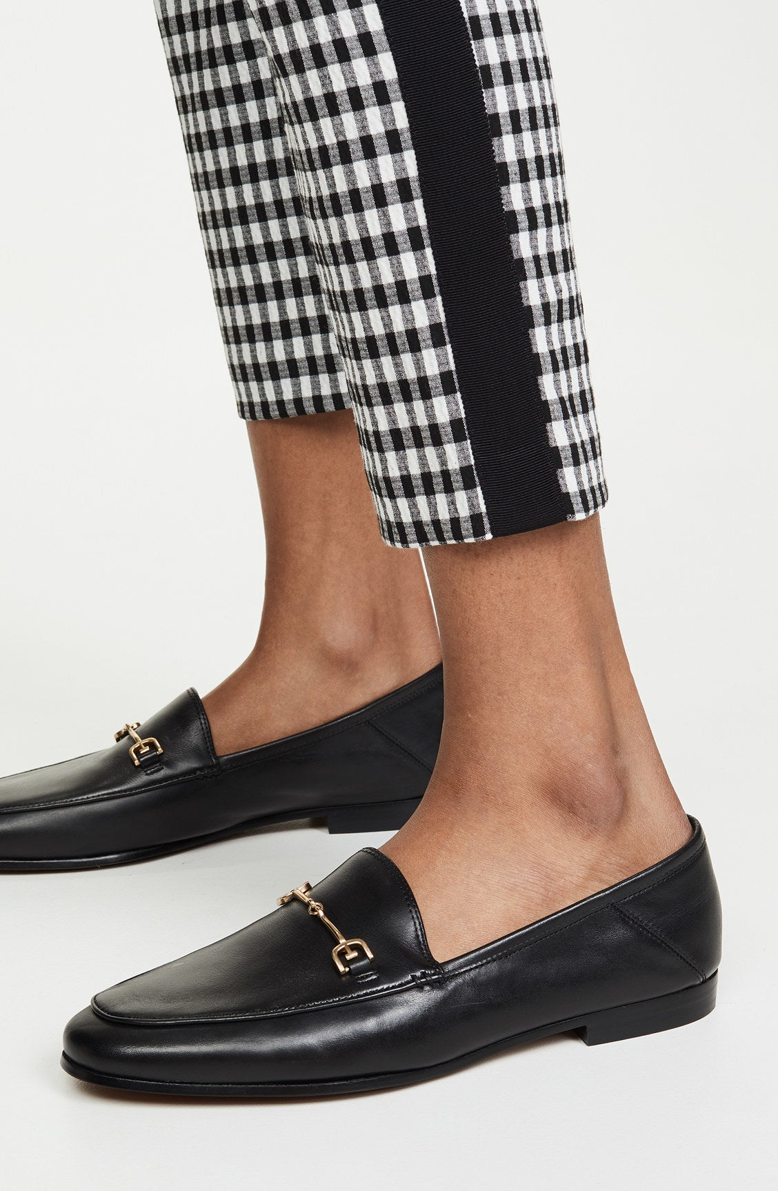 The loafers in black with a small gold metal bar across the top