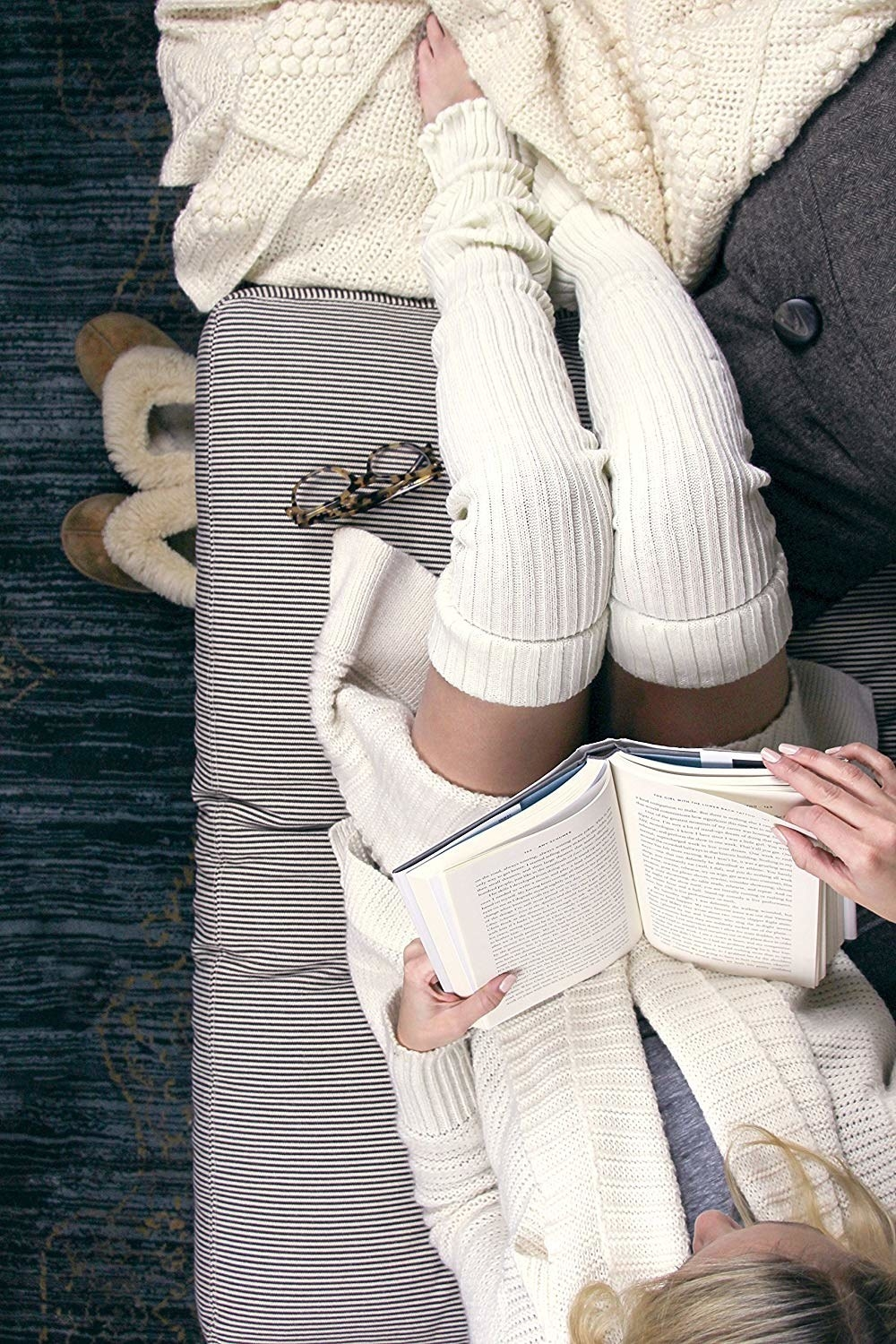 Person reading while wearing leg warmers and a sweater