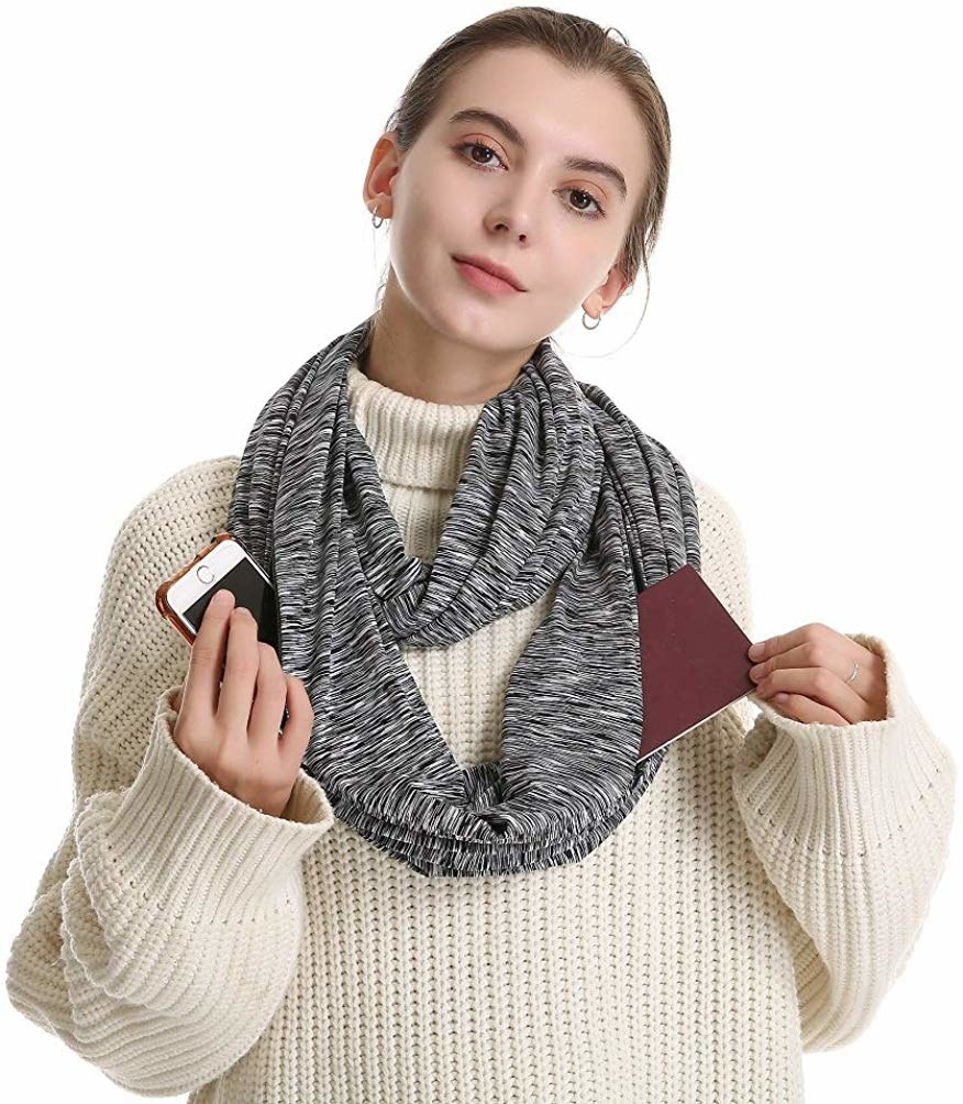 Model in the black and white striped scarf showing their phone and a notebook going into the two pockets