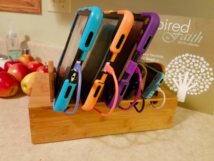 wooden holder with slots fo holding phones and tablets while they charge