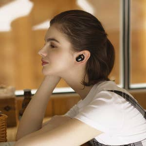 Model with the earbuds in their ear — showing how small and sleek they are