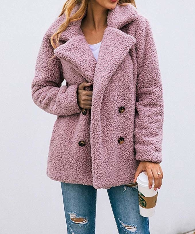 Model wearing the blush pink teddy coat with button up design and large lapels