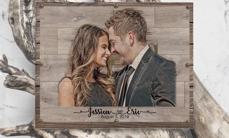 Wood piece of couple smiling beside each other with their names and wedding date written on the bottom