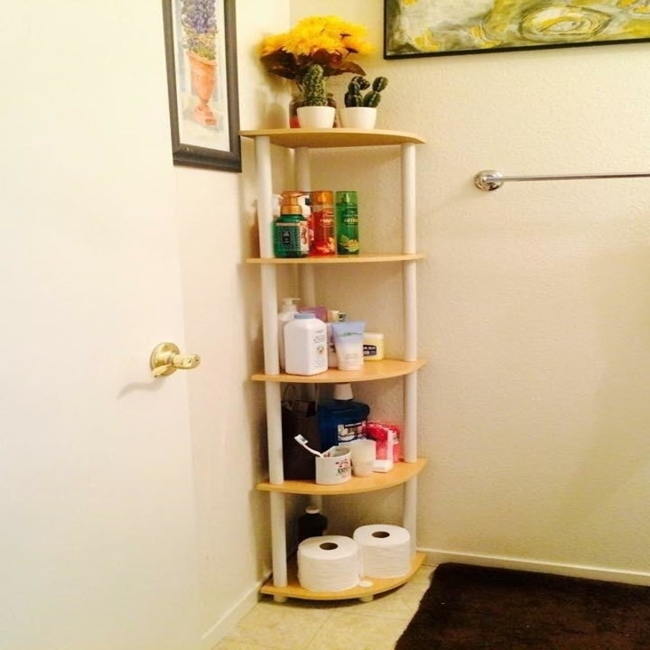 reviewer's shelf in a bathroom, holding toiletries