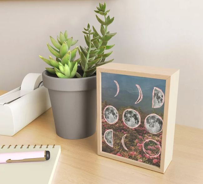 the print featuring a field of flowers, mountains, and illustrated phases of the moon