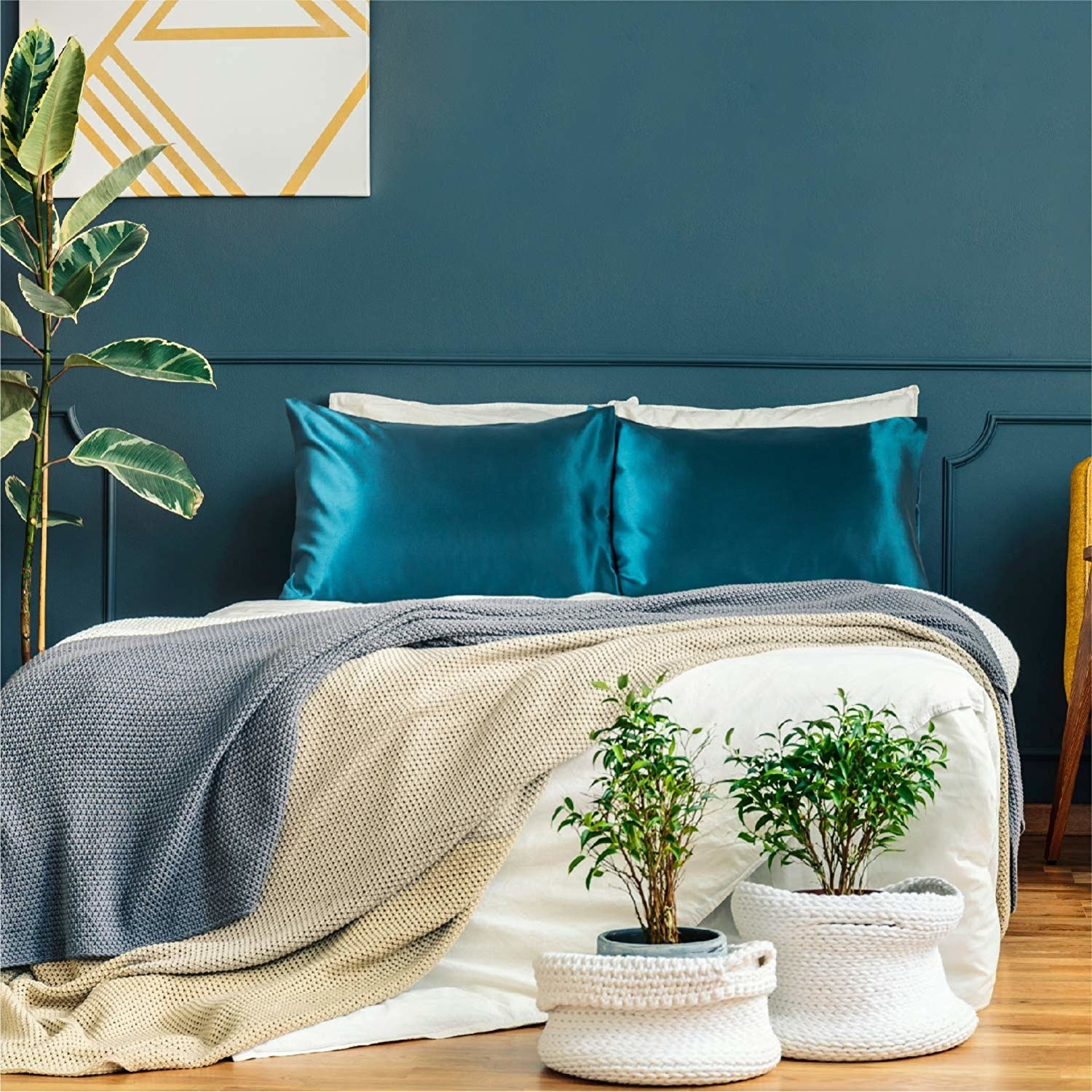 two rich aqua coloured satin pillowcases styled on a bed