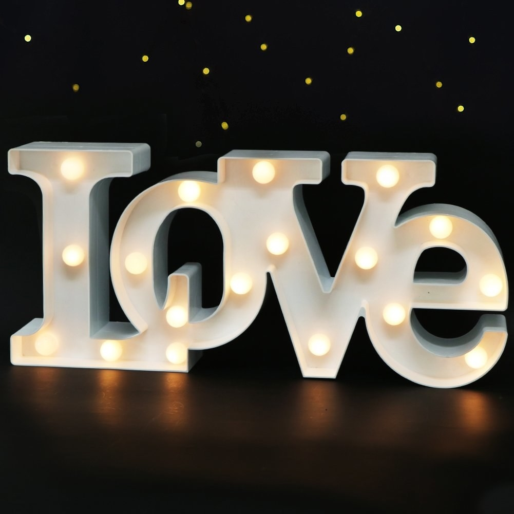White metal light with exposed bulbs spelling out LOVE