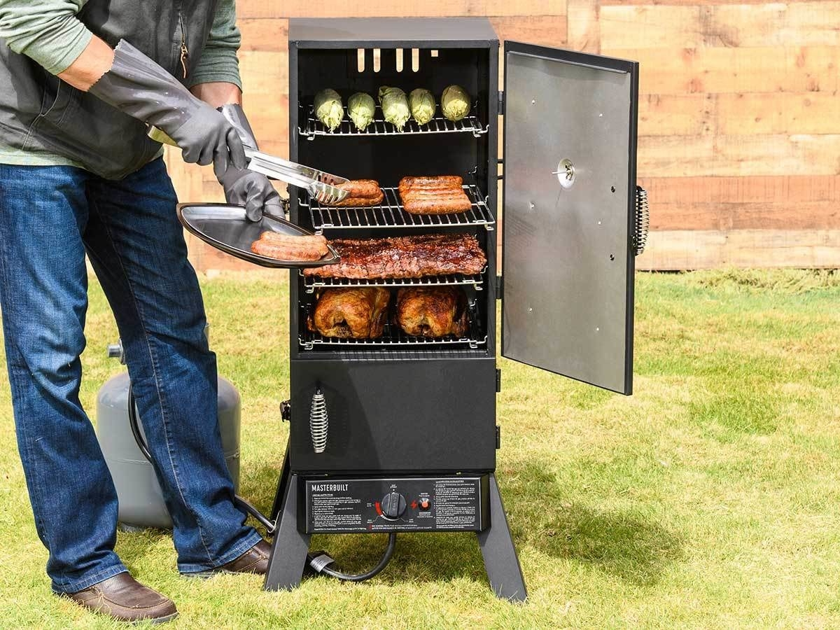 A person taking sausages out of the smoker (which also has two poultry birds, ribs, and corn inside)