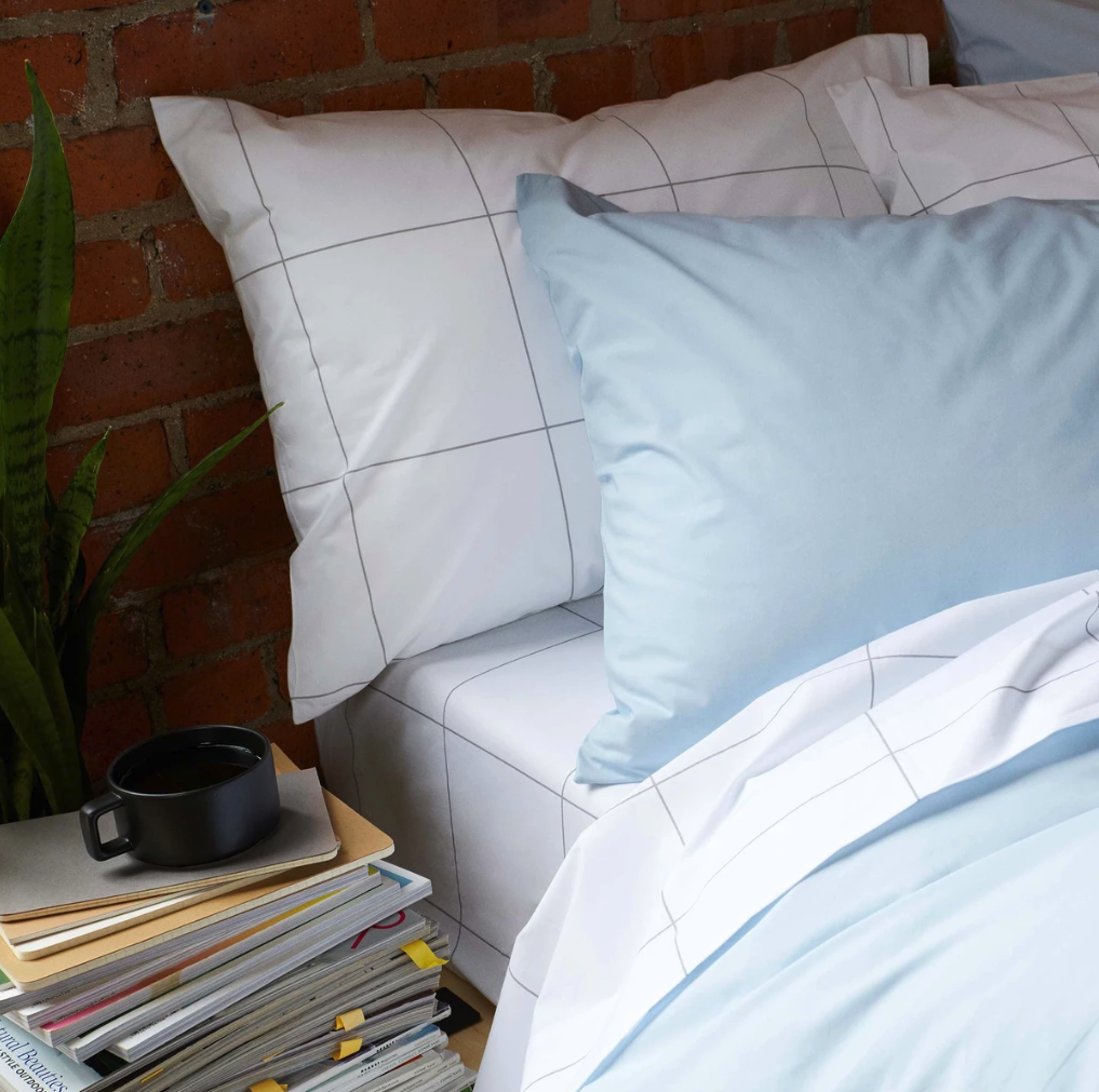 a bed with a sheet set that's white with a gray grid pattern, light blue pillows, and a light blue comforter