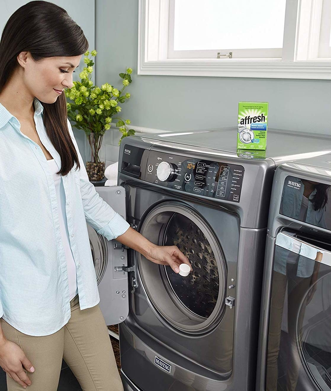 A person putting a washing machine tablet into their washing machine