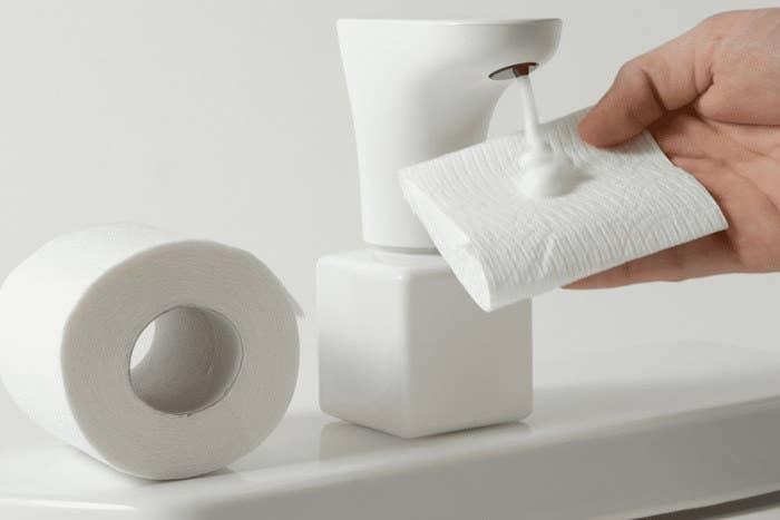 Model holding toilet paper up to Fohm dispenser